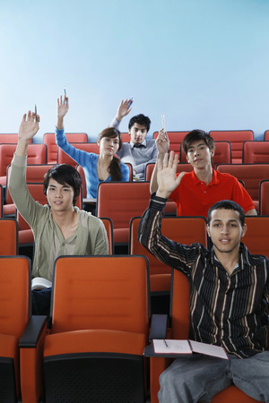 attentiveness: People raising hands in the lecture hall