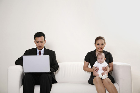 laps: Businessman using laptop, businesswoman with baby sitting on her laps
