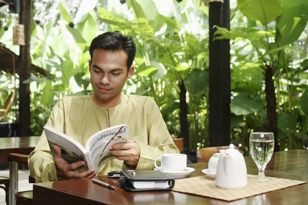 reading magazine: Man reading magazine at restaurant