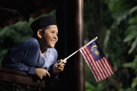 Boy in traditional clothing holding Malaysian flag