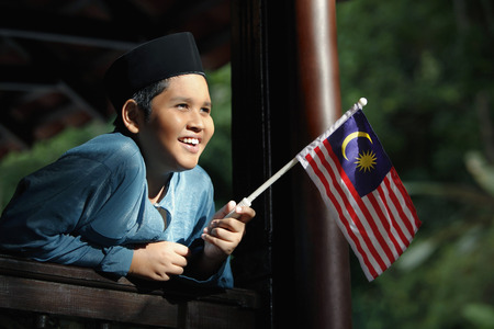 national flag: Boy in traditional clothing holding Malaysian flag