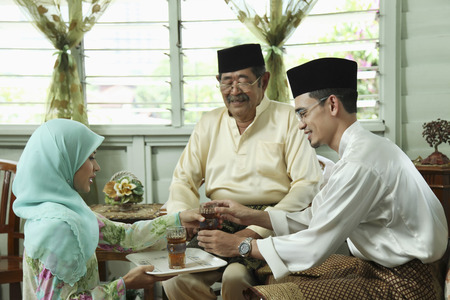 Woman serving senior man and man with drinks