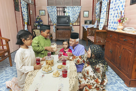 galletas: Hombre mayor y mujer que goza de las galletas con sus nietos