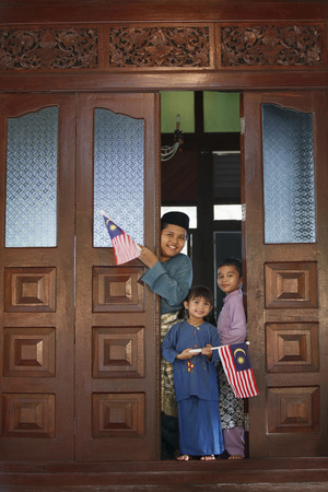 traditional clothing: Boys and girl in traditional clothing holding flags LANG_EVOIMAGES