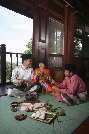 Senior woman teaching man and boy how to wrap ketupat