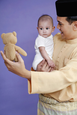 Man showing baby a teddy bear while carrying her LANG_EVOIMAGES