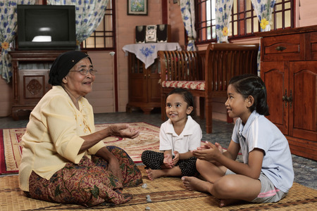 Senior woman playing traditional game with grandchildren