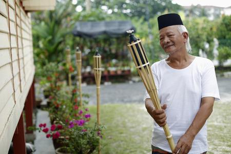 Senior man holding bamboo torch