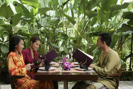 only three people: Man and women reading menu at restaurant