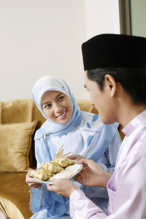 Man and woman holding a plate of ketupat Stock Photo