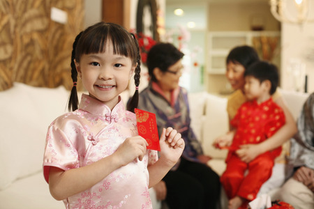 Girl smiling while holding red packet LANG_EVOIMAGES