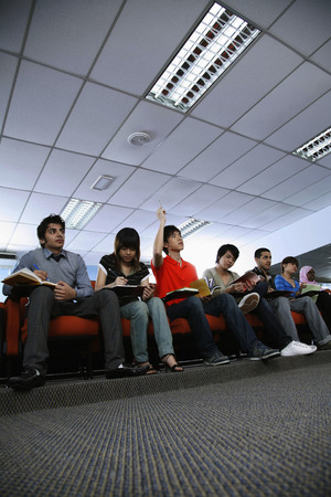 attentiveness: Man raising his hand while listening to a lecture in the classroom LANG_EVOIMAGES