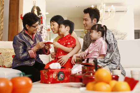 Couple and children getting red packet from senior woman 스톡 콘텐츠