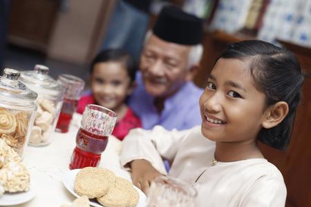 Senior man enjoying traditional cookies with his grandchildren