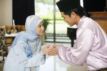 Mann und Frau bei der Begrüßung Hari Raya