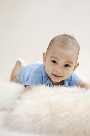 lying forward: Baby lying forward on fur LANG_EVOIMAGES