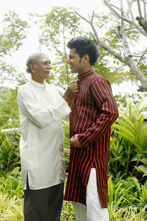 kurta: Senior man helping his son to button his kurta