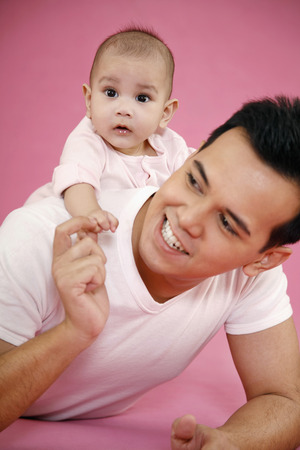lying forward: Man giving baby a piggyback ride while lying forward on the floor