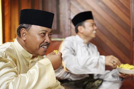 Men eating rice with hands Foto de archivo