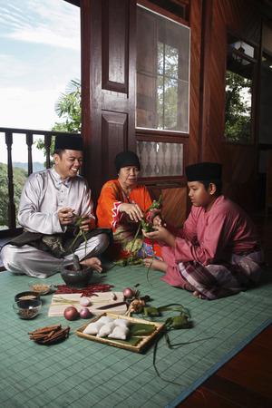 Ältere Frau, die Lehre Mann und Junge, wie man ketupat wickeln