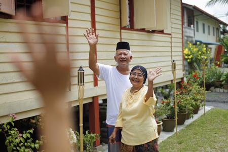 Senior man and woman waving