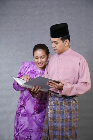traditional clothing: Man and woman in traditional clothing reading document