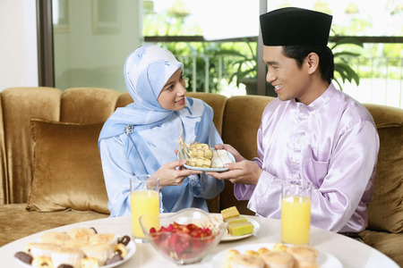 Man and woman holding a plate of ketupat