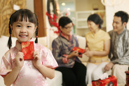 Girl smiling while holding red packet 免版税图像