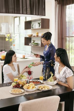 Frau, die grünen Pakete an ihre Freunde während Hari Raya offenen Tür LANG_EVOIMAGES