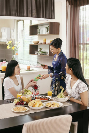 Woman giving green packets to her friends during Hari Raya open house