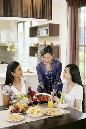 Frau serviert ihren Freunden einige traditionelle Cookies während Hari Raya LANG_EVOIMAGES