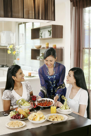 traditional celebrations: Woman serving her friends some traditional cookies during Hari Raya LANG_EVOIMAGES