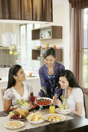 Woman serving her friends some traditional cookies during Hari Raya Stock Photo