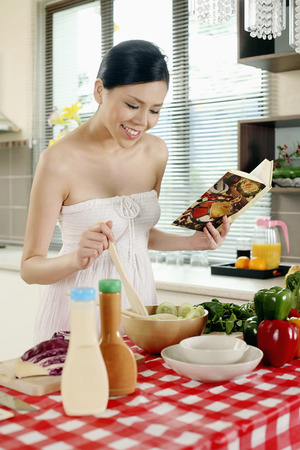 Woman preparing salad while referring to cook book