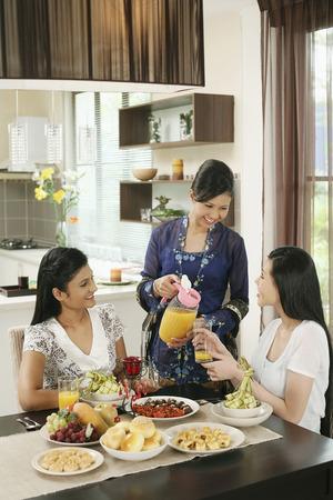 Frau gießt ein Glas Saft für ihre Freundin während Hari Raya offenen Tür LANG_EVOIMAGES