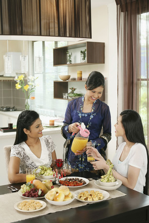 Woman pouring a glass of juice for her friend during Hari Raya open house