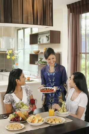 Woman serving her friends some traditional cookies during Hari Raya Reklamní fotografie