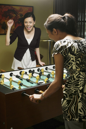foosball: Two women playing foosball LANG_EVOIMAGES