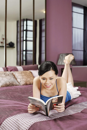lying forward: Woman reading magazine on the bed