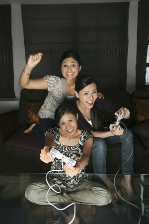 three people only: Women playing video game console