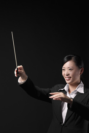 conducting: Woman conducting with baton in hand