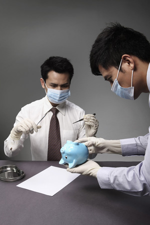 experimenting: Two businessmen experimenting with piggy bank