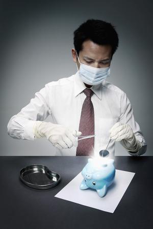 stopper: Businessman removing rubber stopper from piggy banks bottom