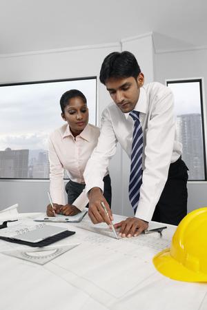Architect drawing on plan, woman watching