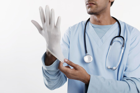 putting: Doctor putting on surgical glove
