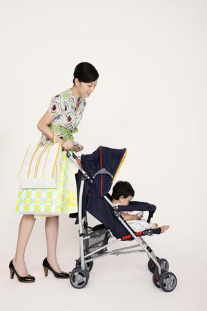 empujando: Mujer empujando bebé en cochecito