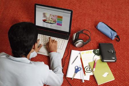 lying forward: Young man lying forward on the floor, using laptop