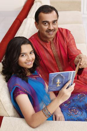 kurta: Teenage girl and man reading greeting card together LANG_EVOIMAGES