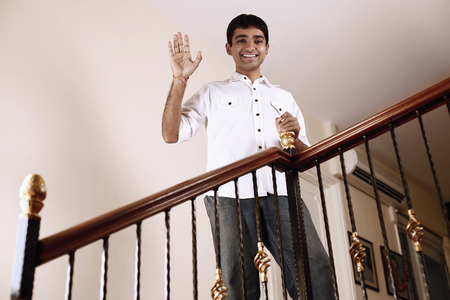 Young man waving from the staircase
