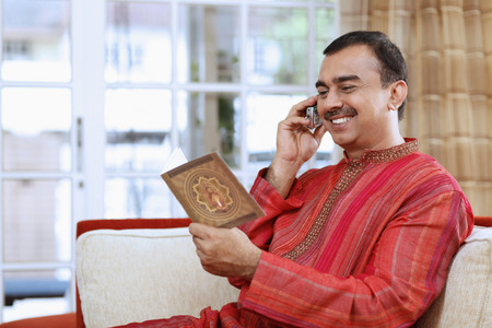 kurta: Man talking on the phone while reading greeting card